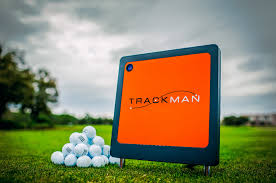 A TrackMan pad is pictured sitting on a course next to some golf balls
